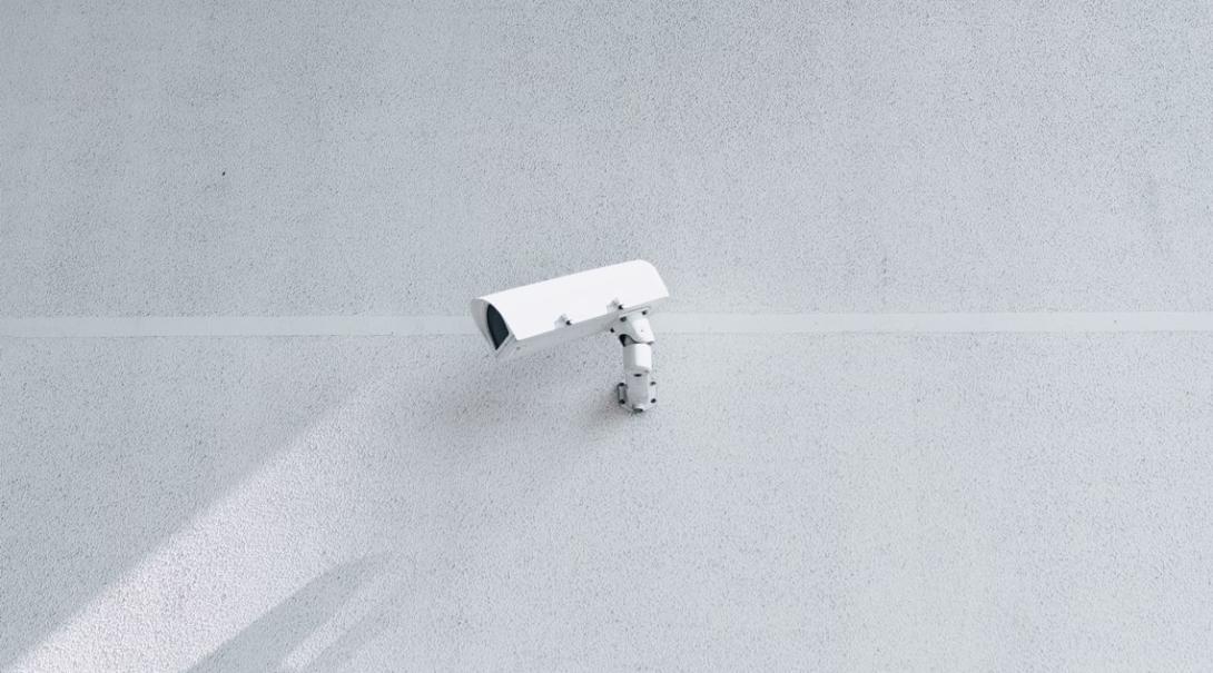 壁に備え付けられた白い監視カメラ